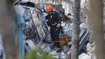 Fire rescue personnel conduct a search and rescue with dogs through the rubble of the Champlain Towers South Condo after the multistory building partially collapsed in Surfside, Fla., Thursday, June 24, 2021. (David Santiago/Miami Herald via AP)