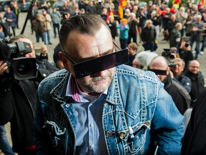 Lutz Bachmann, founder of Germany's anti-Islamic Pegida movement arrives for his trial on April 19, 2016 in Dresden, his eyes covered (AFP Photo/Robert Michael)