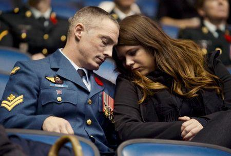 A couple react while watching a broadcast of the funeral service for Cpl Nathan Cirillo at FirstOntario Centre in Hamilton, October 28 2014. REUTERS/Aaron Harris