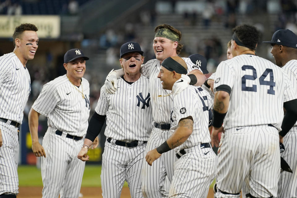 From left, New York Yankees Aaron Judge, Gio Urshela, Clint Frazier, and Rougned Odor, third from left, celebrate with Luke Voit after Voit hit a walk-off RBI single to give the Yankees a 6-5 win in the ninth inning of a baseball game against the Kansas City Royals, Wednesday, June 23, 2021, at Yankee Stadium in New York. (AP Photo/Kathy Willens)
