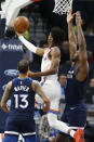 Oklahoma City Thunder's Shai Gilgeous-Alexander, center, of Canada, lays up a shot as Shabazz Napier, left, and Minnesota Timberwolves' Noah Vonleh defend in the first half of an NBA basketball game Monday, Jan. 13, 2020, in Minneapolis. (AP Photo/Jim Mone)