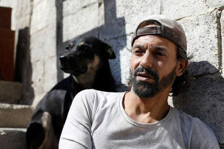 FILE PHOTO: Abu Nimr, 36, is pictured with his dog in Yarmouk Palestinian camp in Damascus