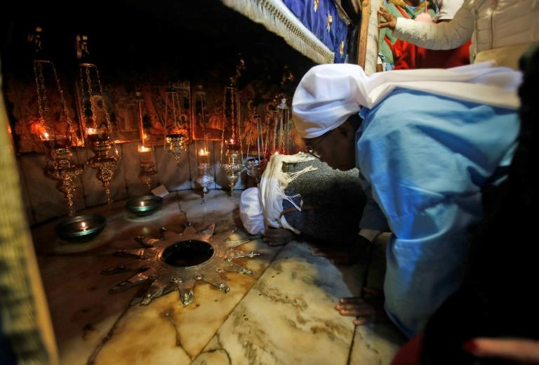 A Christian pilgrim kisses the 14 pointed silver star, believed to be the exact spot where Jesus Christ was born, in the Grotto of the Church of the Nativity in Bethlehem