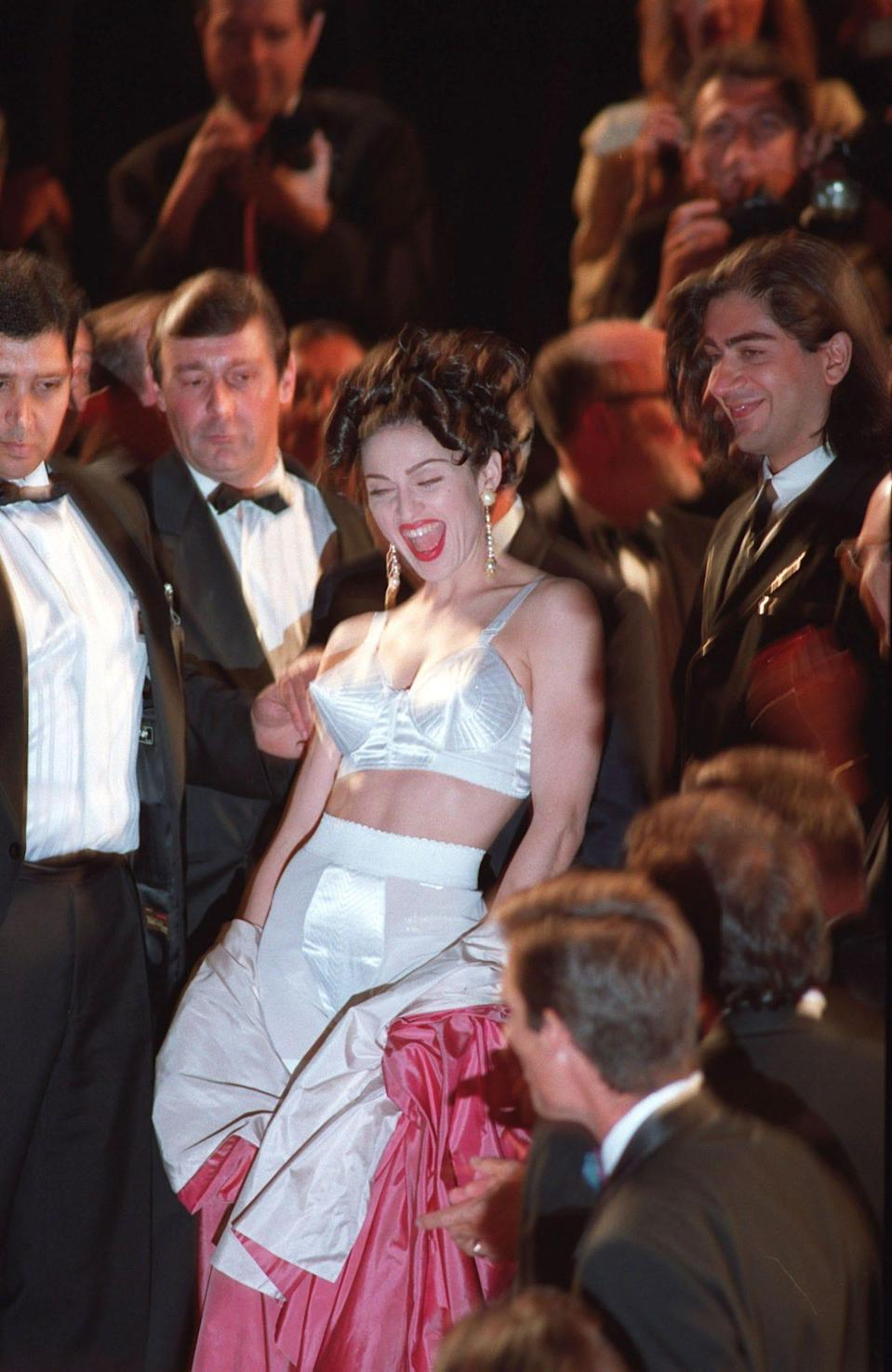Madonna wears a white bra, matching shorts, and a pink robe at the 1991 Cannes Film Festival.
