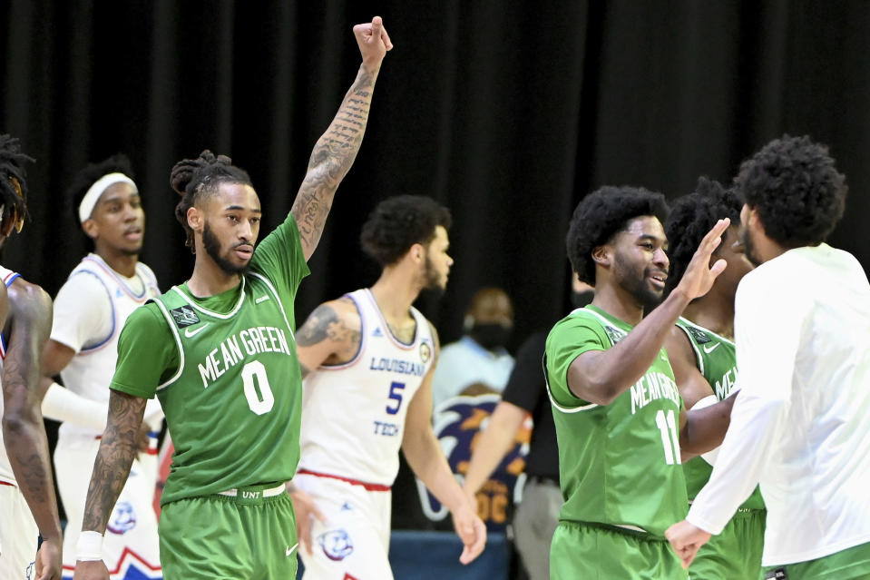 North Texas guards James Reese (0) and JJ Murray (11) celebrate after their 54-48 win over Louisiana Tech in an NCAA college basketball game at the Conference USA men's tournament in Frisco, Texas, Friday, March 12, 2021. North Texas won 54-48. (AP Photo/Matt Strasen)