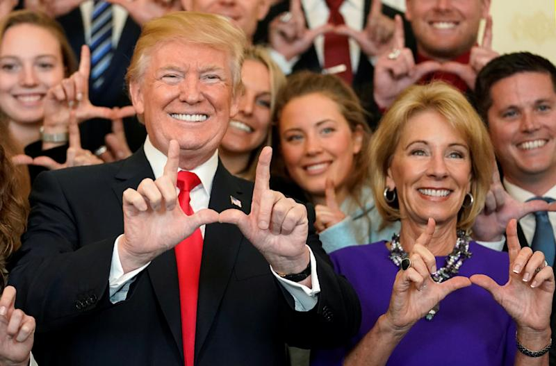 "President Donald Trump and Education Secretary Betsy DeVos make ""U"" symbols with their hands while posing with the Utah Skiing team at the White House, Nov. 17, 2017."
