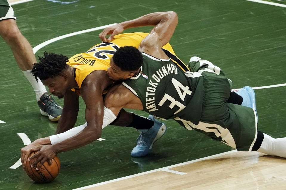 Miami Heat's Jimmy Butler and Milwaukee Bucks' Giannis Antetokounmpo battle for a loose ball during the second half of Game 1 of their NBA basketball first-round playoff series Saturday, May 22, 2021, in Milwaukee. (AP Photo/Morry Gash)
