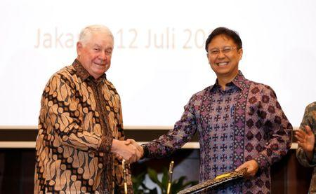 Freeport-McMoRan Chief Executive Officer Richard Adkerson (L), and PT Inalum Chief Executive Budi Gunadi Sadikin shake hands after signing an initial agreement for the state-owned mining company Inalum to take a controlling stake in Freeport's local unit, in Jakarta, Indonesia, July 12, 2018. REUTERS/Darren Whiteside