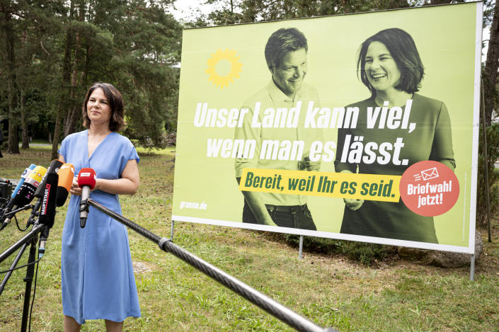 Annalena Baerbock, left party leader and candidate for chancellor, arrives for the unveiling of a large-scale Green Party poster in Michendorf, Germany, Monday, July 26, 2021. With this, the Greens set the starting signal for the nationwide billboarding for the Bundestag election 2021. ( Fabian Sommer/dpa via AP)