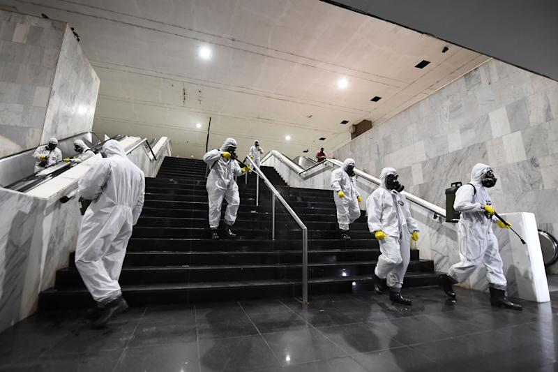 Brazilian soldiers disinfect the Subway Central Station and its surroundings, as a measure against the spread of the coronavirus, COVID-19, pandemic in Brasilia, early on March 29, 2020. - A federal court in Rio de Janeiro on Saturday banned the government from disseminating propaganda against confinement measures aimed at controlling the coronavirus pandemic. The campaign video encourages people not to stop their normal lives, despite health ministry figures show that COVID-19 has claimed almost 100 lives and affected close to 3,500 people in Brazil. (Photo by EVARISTO SA / AFP) (Photo by EVARISTO SA/AFP via Getty Images)
