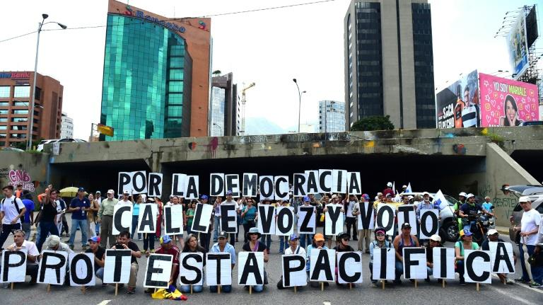 Opposition activists protest in Caracas on August 12, 2017