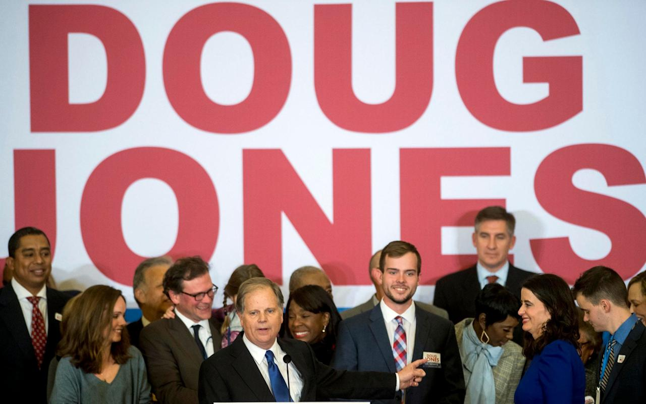 """Doug Jones, the Democrat who pulled off a stunning upset victory in Alabama's nail-biter Senate contest on Tuesday, is considered a champion for civil rights in a state that played a seminal role in the 1960s movement for racial equality. Mr Jones' supporters erupted in cheers and jubilation as it became clear their portly, balding candidate had become the first Alabama Democrat to win a US Senate seat in 25 years. """"I am truly, truly overwhelmed,"""" Mr Jones said as aides and volunteers hugged and cheered. """"We have shown the country the way that we can be unified."""" It came at the bitter end of a vitriolic campaign centered on MrJones's Republican rival, Roy Moore, a Christian conservative accused of preying on teenage girls years before. Former White House strategist Steve Bannon had championed Mr Moore as an anti-establishment fighter, and ultimately President Donald Trump threw his weight behind the embattled former judge even as other Republican leaders kept their distance. But Trump was quick to congratulate Jones, even though Moore had yet to concede defeat. """"A win is a win,"""" Trump said on Twitter. A long shot Mr Jones, 63, had never run for office before throwing his hat into the ring in Alabama - and as a believer in climate change and abortion rights was initially given no chance in the solidly Republican state, where Trump defeated Democrat Hillary Clinton by 28 points. The former US attorney earned his reputation with the successful prosecution of two members of the Ku Klux Klan for a 1963 dynamite attack on a black church in Birmingham, Alabama. The infamous Sunday morning bombing of the 16th Street Baptist Church, which left four young girls dead, helped galvanize support for the civil rights movement and came just months after Martin Luther King Jr was arrested for organizing non-violent protests against racial segregation in Birmingham. Doug Jones holds his granddaughter as he celebrates with supporters at the election night party in Birmingham Credit: R"""