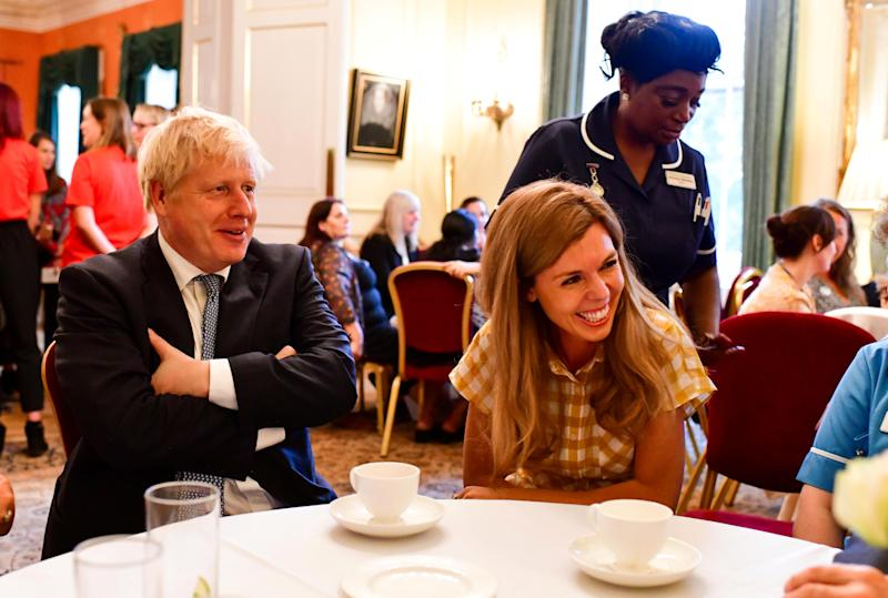 Britain's Prime Minister Boris Johnson sits next to his partner Carrie Symonds as he hosts a reception to thank hospice staff at 10 Downing Street, in London, Britain August 12, 2019. Picture taken August 12, 2019. 10 Downing Street/Handout via REUTERS THIS IMAGE HAS BEEN SUPPLIED BY A THIRD PARTY. MANDATORY CREDIT