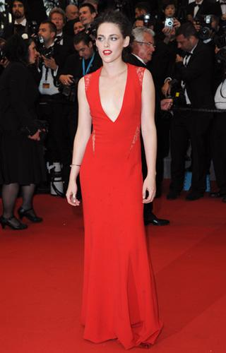 Who: Kristen Stewart What: Red Reem Acra gown Where: Cosmopolis premiere Why We Love It: As much as Stewart seems to be gritting her teeth on the red carpet, she's been consistently upping her fashion game. After throwing down some amazing floral print pants and a gorgeous embellished Balenciaga gown earlier in the fest, the actress stunned in this low-cut number in high-octane red. Ironically, it's her apparent indifference that's made Stewart's festival looks work so well: the slightly ratty hair, insouciant slouch and rarely an accessory, save a Cartier Juste un Clou bracelet.  Photo by Keystone Press