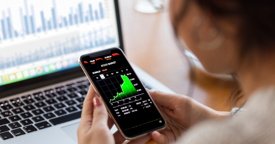 A young woman holds a phone with stock price changes displayed on the screen.