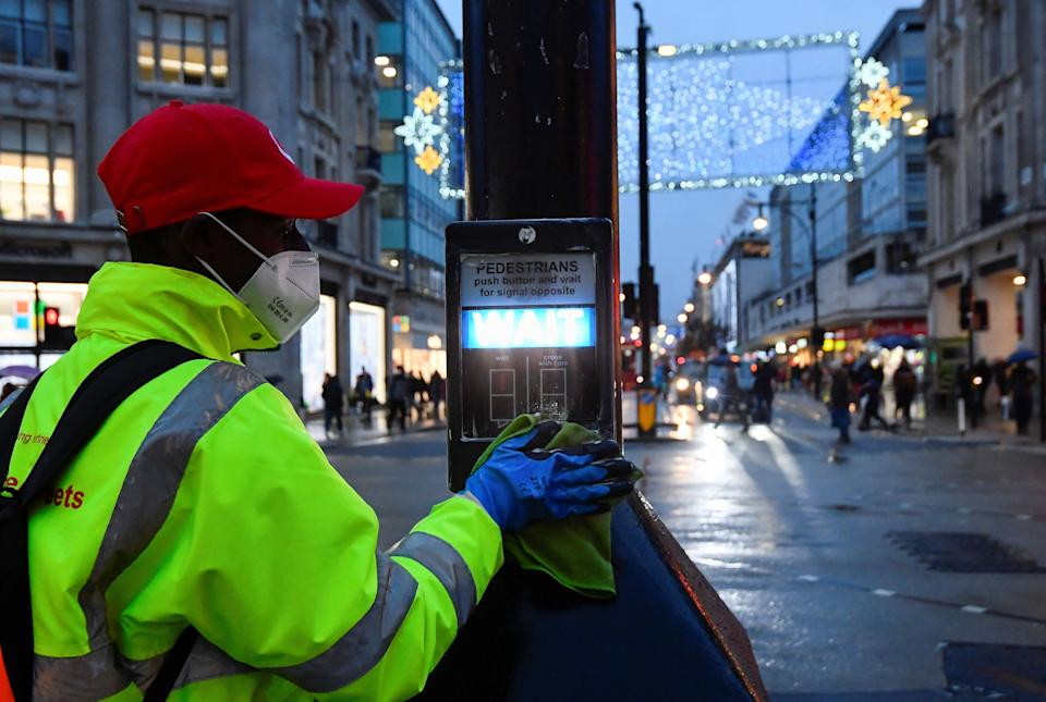A street cleaner pictured in December sanitising the button on a pedestrian crossing (Photo: Toby Melville / Reuters)
