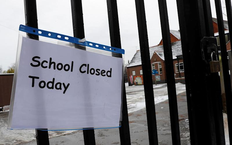 A closed sign hangs on the gate of a school following snow fall - REUTERS