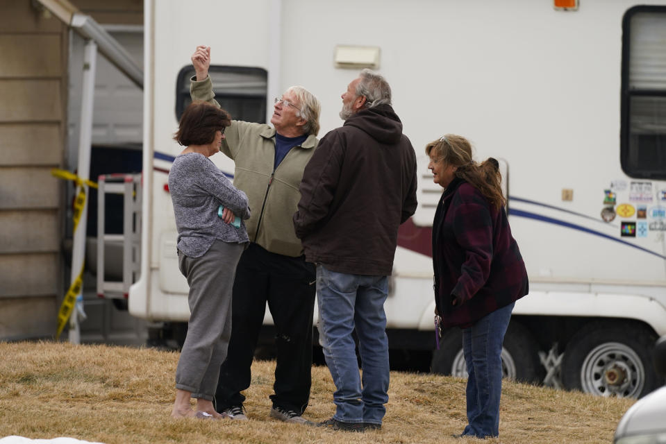 Neighbors gather on the lawn next to the home of Kirby Klements after a piece of debris from an airplane crushed the man's pickup truck parked next to his home in Broomfield, Colo., as the plane shed parts while making an emergency landing at nearby Denver International Airport Saturday, Feb. 20, 2021. (AP Photo/David Zalubowski)