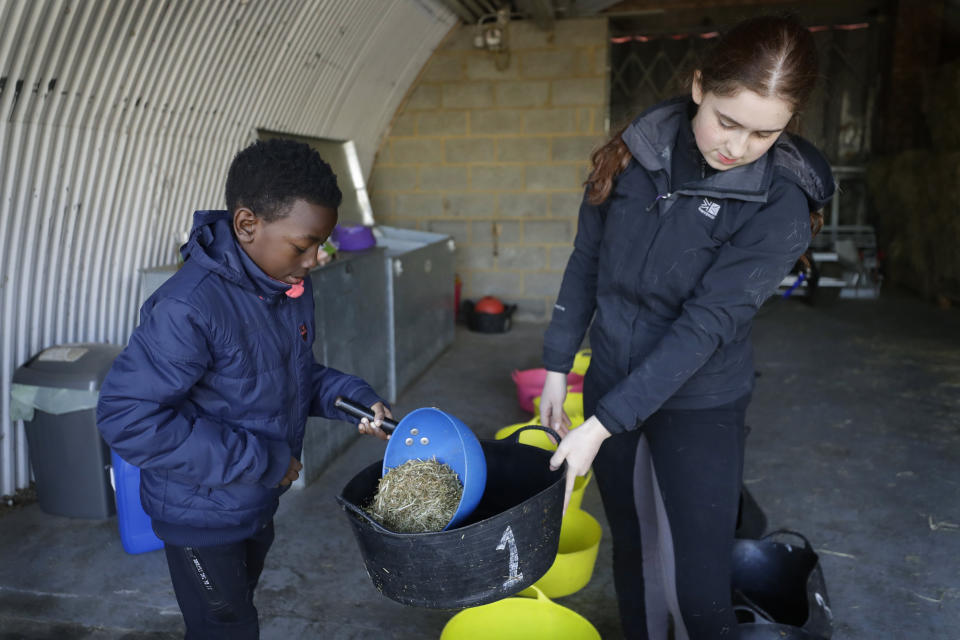 Shaddai Mcleod, 9, left, and Manuela Jimenez, 15, prepare feed buckets for the horses at Ebony Horse Club in Brixton, south London, Sunday, April 18, 2021. In the midst of south London's hustle and bustle, only a 10-minute walk from a subway station, is a school where children are encouraged to horse around. The Ebony Horse Club provides 140 rides per week to children in the local community offering them the opportunity to learn important life skills along with horseback riding. (AP Photo/Kirsty Wigglesworth)