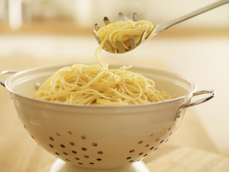 Close up of spoon scooping spaghetti in colander
