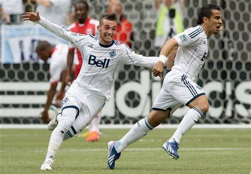 Vancouver Whitecaps' Russell Teibert, left, and Camilo Sanvezzo, of Brazil, celebrate Sanvezzo's goal against the Portland Timbers during the first half of an MLS soccer game in Vancouver, British Columbia on Saturday, May 18, 2013. (AP Photo/ The Canadian Press, Darryl Dyck)
