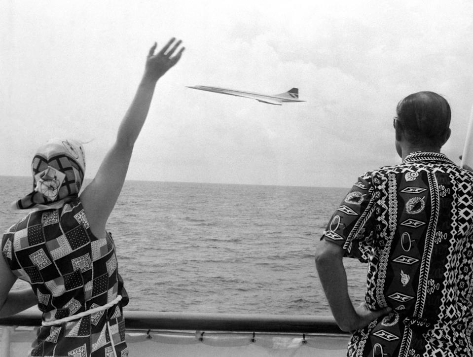 Queen Elizabeth II and the Duke of Edinburgh wave as Concorde flies by the Royal Yacht Britannia as the royal couple neared Barbados.