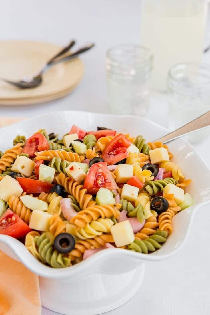 """<p>This summer salad is colorful, fresh, and full of seasonal flavors. Complete with sharp cheddar cheese, cucumbers, and an Italian salad dressing, this pasta is the ideal picnic pairing. This recipe can feed six to eight people, so you can either cut it in half and save the rest for later, or make a big batch and nosh on it throughout the week.</p> <p><strong>Get the recipe:</strong> <a href=""""https://aclassictwist.com/summer-pasta-salad-recipe/"""" class=""""link rapid-noclick-resp"""" rel=""""nofollow noopener"""" target=""""_blank"""" data-ylk=""""slk:summer pasta salad"""">summer pasta salad</a></p>"""