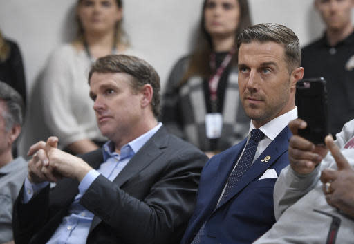 Newly signed Washington Redskins quarterback Alex Smith, right, and the NFL football team's coach, Jay Gruden, left, listen during a news conference Thursday, March 15, 2018, in Ashburn, Va. (AP Photo/Nick Wass)