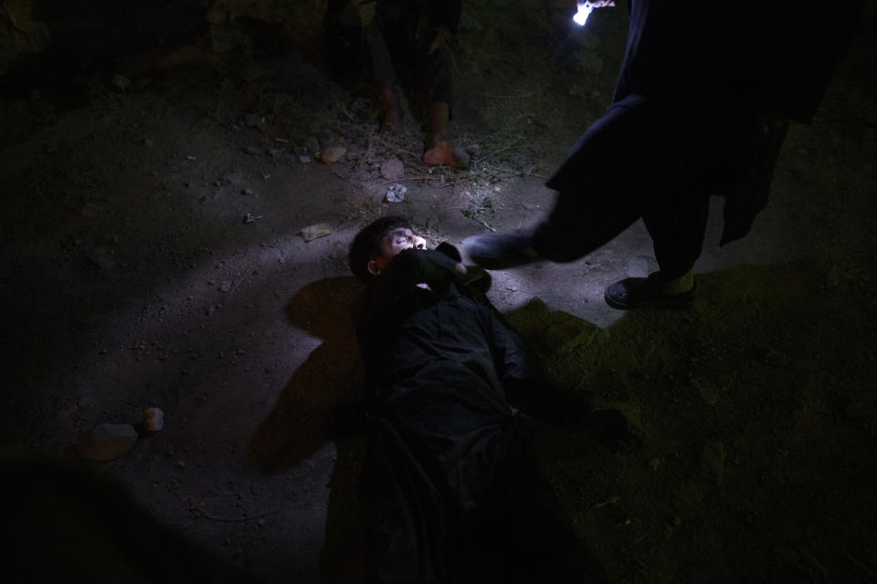 A Taliban fighter kicks a man sleeping on the ground during a police operation to detain drug users in Kabul, Afghanistan, Friday, Oct. 1, 2021. The Taliban are shifting from being warriors to an urban police force. (AP Photo/Felipe Dana)