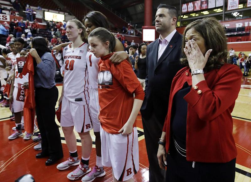 Rutgers head coach C. Vivian Stringer wipes a tear as she stands with athletic director Tim Pernetti and her team to celebrate Stringer's 900th career win in an NCAA college basketball game Tuesday, Feb. 26, 2013, in Piscataway, N.J., Rutgers defeated South Florida 68-56. (AP Photo/Mel Evans)