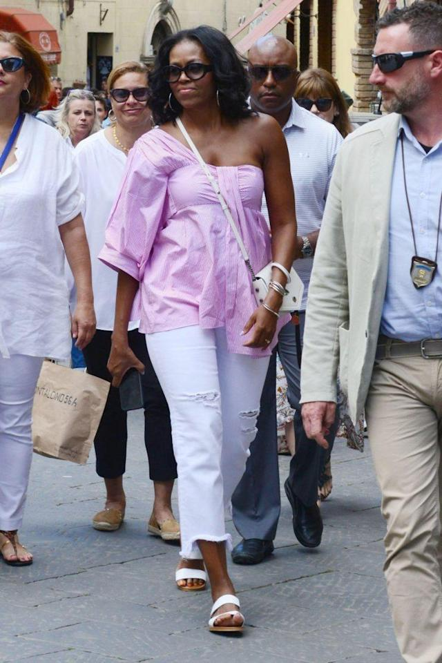 Michelle Obama wearing a pink TEIJA shirt with AG jeans while in Italy. (Photo: AKM-GSI)
