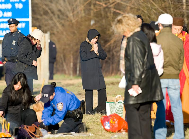 Victim's family members participate in a Buddhist service at the location of the tour bus crash, Saturday, March 19, 2011 in the Bronx borough of New York. Fifteen people were killed March 12, 2011, when a tour bus returning to New York from Connecticut overturned and was split in two by a sign support pole. (AP Photo/Stephen Chernin)