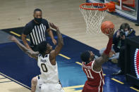 Oklahoma guard De'Vion Harmon (11) shoots past West Virginia guard Kedrian Johnson (0) during the first half of an NCAA college basketball game Saturday, Feb. 13, 2021, in Morgantown, W.Va. (AP Photo/Kathleen Batten)
