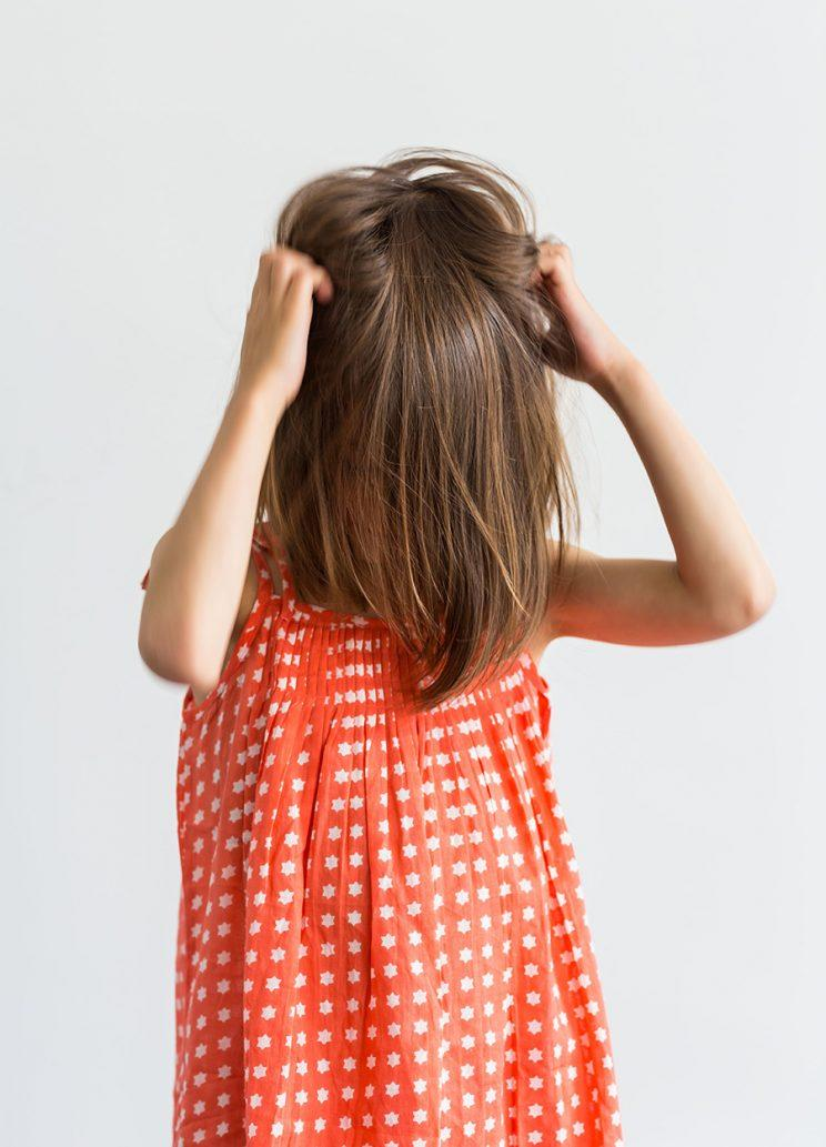 A girl with bangs covering her face scratches her head.