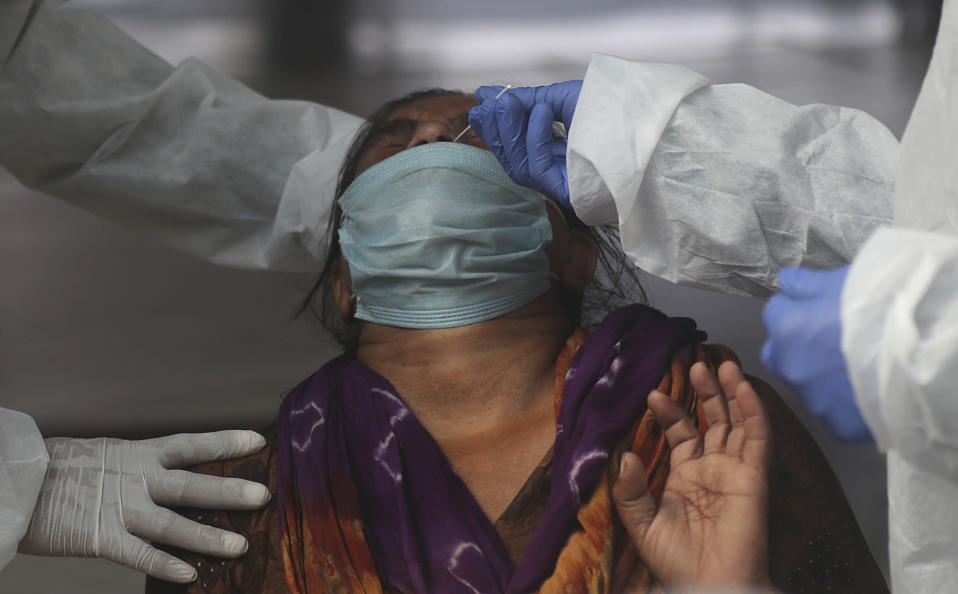 Health workers takes a nasal swab sample of a woman passenger to test for COVID-19 at a train station in Mumbai, India, Friday, Nov. 27, 2020. India has more than 9 million cases of coronavirus, second behind the United States. (AP Photo/Rafiq Maqbool)