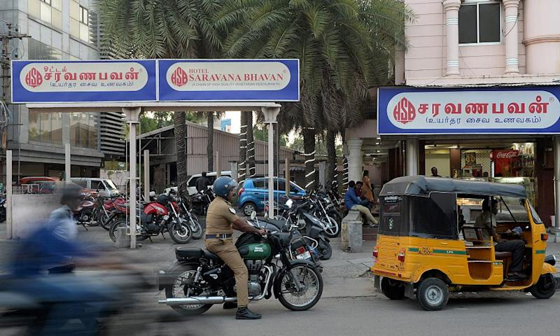 Vehicles pass a branch of Saravana Bhavan in Chennai