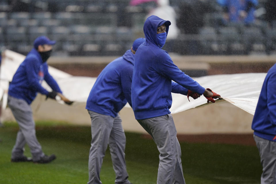 New York Mets employees put a tarp over the field during a delay in the first inning of a baseball game against the Miami Marlins at Citi Field, Sunday, April 11, 2021, in New York. The game was delayed at the top of the first inning due to rain. (AP Photo/Seth Wenig)