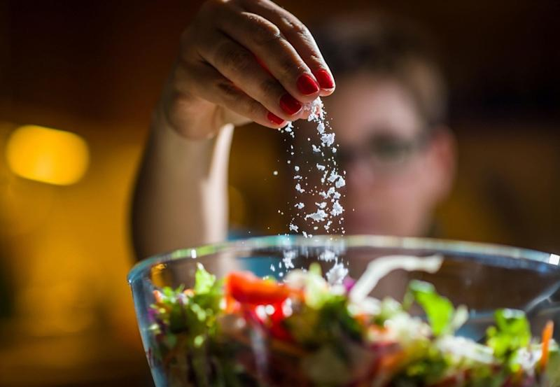 Woman preparing healthy salad in kitchen, adding salt to the bowl