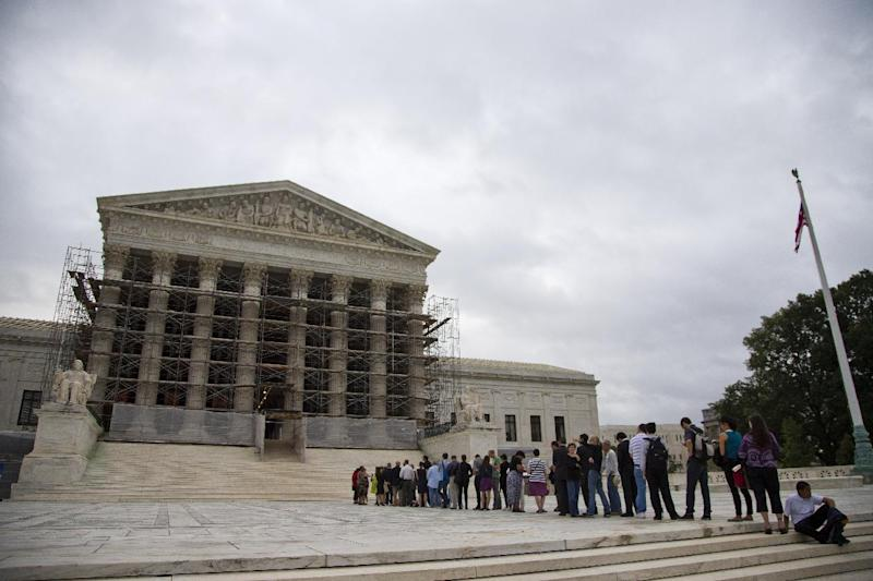 People wait in line for the beginning of the Supreme Court 2013-2014 opening term in Washington, Monday, Oct. 7, 2013. In its first major campaign finance case since the Citizens United ruling in 2010, the Supreme Court is considering whether to undo some limits on contributions from the biggest individual givers to political campaigns. The justices will hear arguments Tuesday, the second day of their new term, in a dispute between the Obama administration and Republicans who are challenging the contribution limits as a violation of First Amendment rights. (AP Photo/ Evan Vucci)