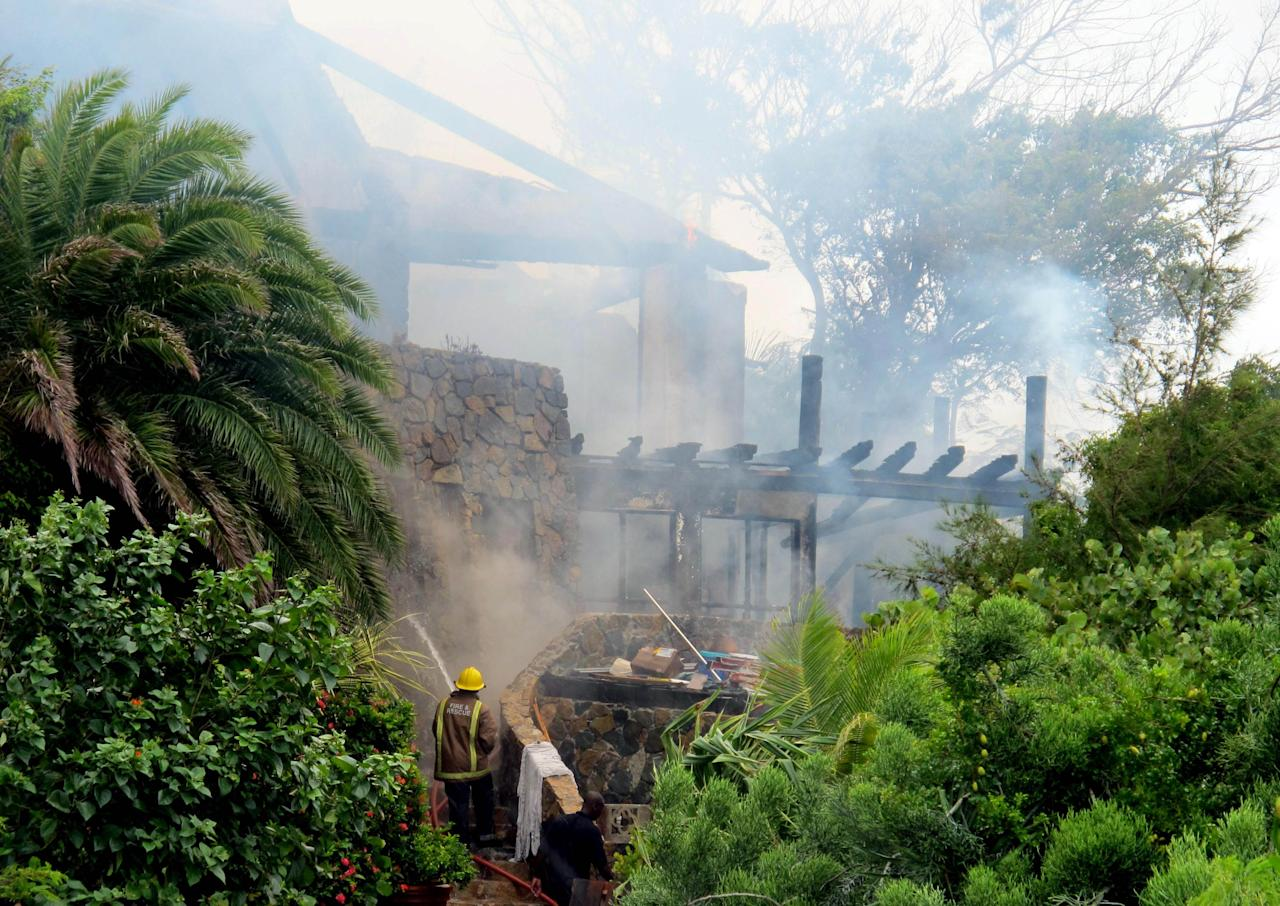 In this image issued Monday Aug. 22, 2011 by Virgin Limited Edition shows a firefighter spraying British entrepreneur's Sir Richard Branson's luxury home, on Necker Island, in the Caribbean, which was damaged by a fire which ripped through the luxury home. Guests including Academy Award-winning actress Kate Winslet escaped uninjured when fire destroyed Richard Branson's Caribbean home during a tropical storm Monday, said the British businessman. The Virgin Group boss said about 20 people, including Winslet and her children, were staying in the eight-bedroom Great House on Necker, his private isle in the British Virgin Islands. (AP Photo/Virgin Limited Edition/PA) UNITED KINGDOM OUT NO SALES NO ARCHIVE EDITORIAL USE ONLY