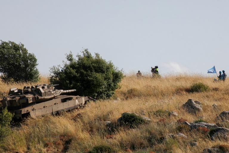 """Lebanese army and UNIFIL soldiers watch on June 2, 2020 from the Lebanese village of Adaisseh as an Israeli army tank takes part in routine manuevers near the """"blue line"""", which marks Israel's withdrawal from southern Lebanon in 2000"""