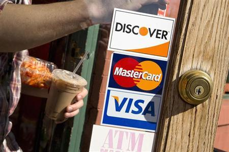 A coffee shop displays signs for Visa, MasterCard and Discover in Washington