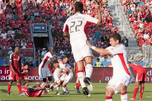 New England Revolution's Chris Tierney (8) is mobbed by teammates after scoring the game-tying goal on stoppage time against Toronto FC during second half MLS soccer action in Toronto on Saturday, June 23, 2012. The match ended 2-2. (AP Photo/The Canadian Press, Chris Young)