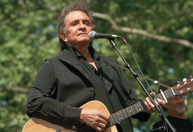 """FILE - In this May 23, 1993 file photo, Johnny Cash performs at a benefit concert in Central Park in New York. Cash's album, """"Out Among the Stars,"""" comprised of 12 studio recordings recently discovered, is releasing March 25, 2014. (AP Photo/Joe Tabacca, File)"""