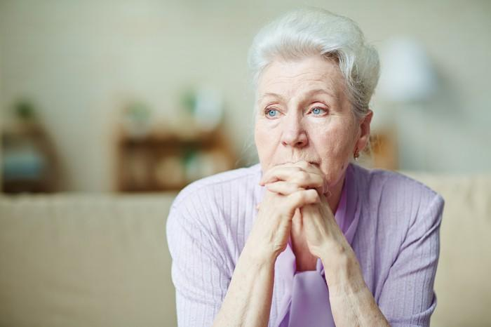 Senior woman with hands clasped looking concerned