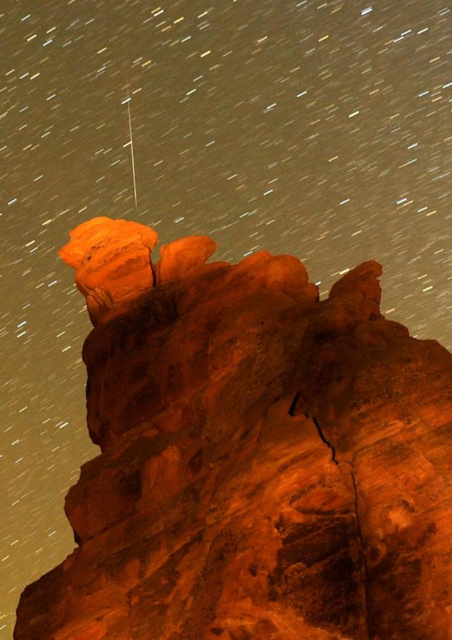 VALLEY OF FIRE STATE PARK, NV - DECEMBER 14: A Geminid meteor streaks above one of the peaks of the Seven Sisters rock formation early December 14, 2010 in the Valley of Fire State Park in Nevada. The meteor display, known as the Geminid meteor shower because it appears to radiate from the constellation Gemini, is thought to be the result of debris cast off from an asteroid-like object called 3200 Phaethon. The shower is visible every December. (Photo by Ethan Miller/Getty Images)