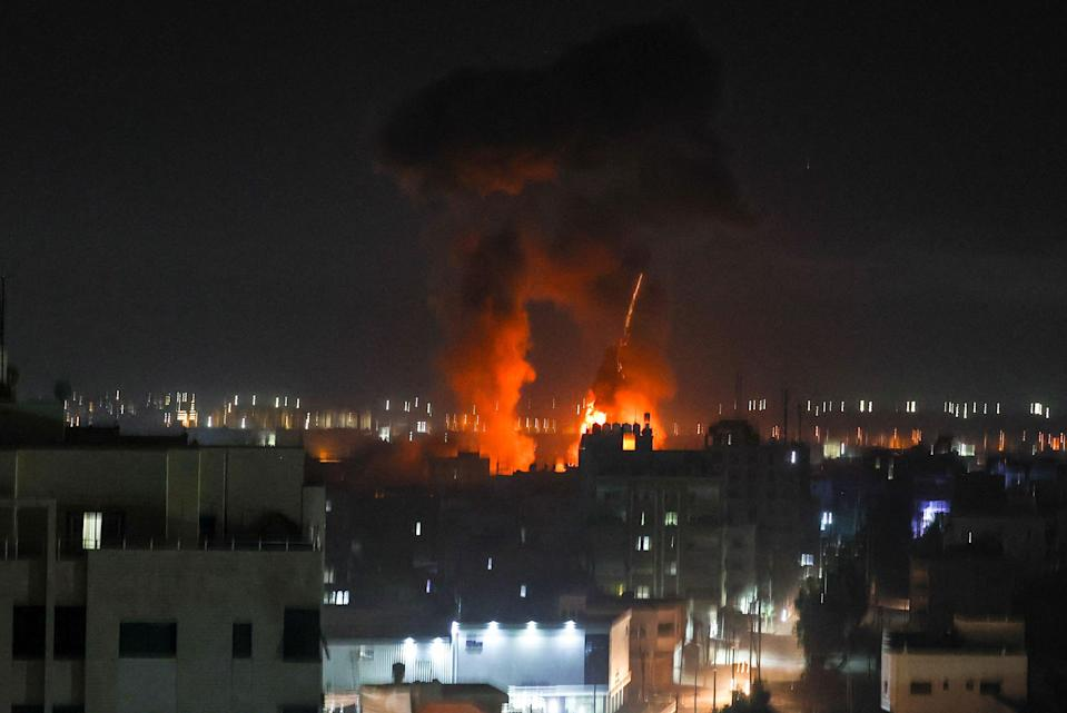 Explosions light-up the night sky above buildings in Gaza City (AFP via Getty Images)