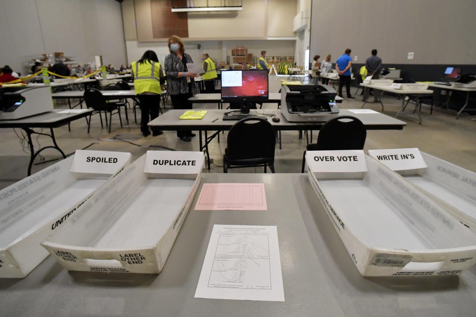Cobb County Election officials prepare for a recount, Tuesday, Nov. 24, 2020, in Marietta, Ga. County election workers across Georgia have begun an official machine recount of the roughly 5 million votes cast in the presidential race in the state. The recount was requested by President Donald Trump after certified results showed him losing the state to Democrat Joe Biden by 12,670 votes, or 0.25% (AP Photo/Mike Stewart)
