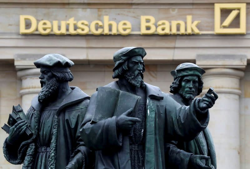 FILE PHOTO: A statue is pictured next to the logo of Germany's Deutsche Bank in Frankfurt