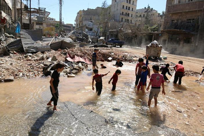 <p>Children play with water from a burst water pipe at a site hit yesterday by an air strike in Aleppo's rebel-controlled al-Mashad neighborhood, Syria, Sept. 30, 2016. (Photo: Abdalrhman Ismail/Reuters)</p>